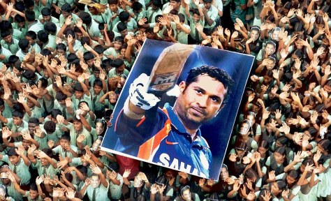 Students hold a huge poster of Sachin Tendulkar after the master blaster scored 100 centuries in international cricket. (Source : dailymail.co.uk)