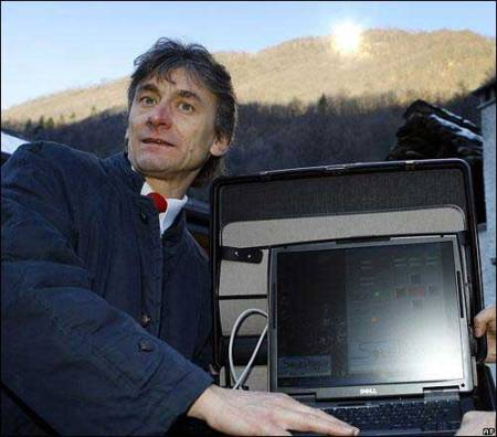 The mayor of Viganella, Italy, holds a computer that controls a giant mirror on the hillside behind