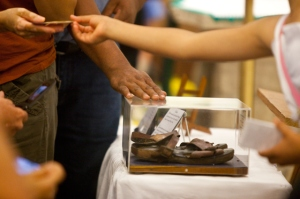 A worshipper touches the case around Mother Teresa's sandals