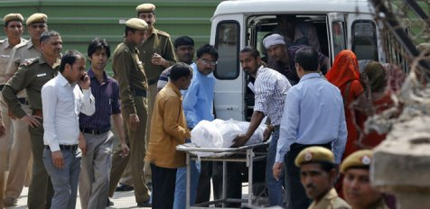 Hospital staff and relatives load the body of Ram Singh