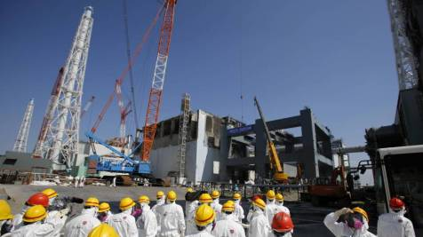Radioactive route: Journalists in protective gear are taken to the No. 4 reactor building at the Fukushima No. 1 nuclear plant on March 6. (Photo:  AP)