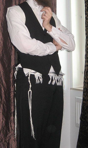 An Orthodox Jewish man wearing a Wool Tallit Katan under his vest
