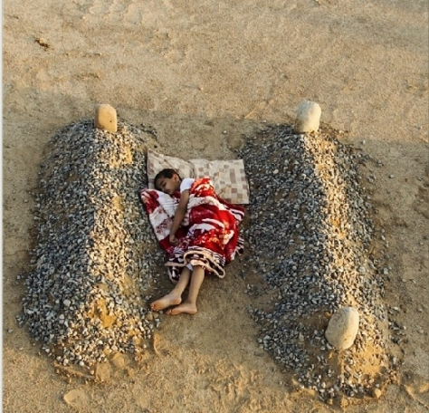 A little boy from Syria sleeping between the graves of his parents. (Photo by abdulaziz_099)