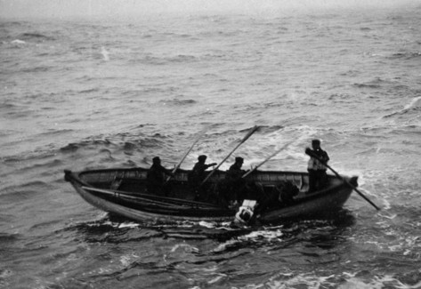 Members of a rescue crew in a whaling boat attempt to retrieve the floating body of a Titanic victim. Photograph by Joseph H. Bailey. (Source: channel.nationalgeographic.com)