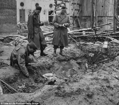 LIFE correspondent Percy Knauth sifting through the dirt and debris in the shallow shell hole where the bodies of Hitler and Eva Braun were thought to have been burned after their suicides. (Source: dailymail.co.uk)