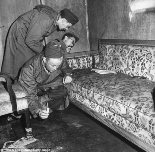 With only candles to light their way, war correspondents examine a couch stained with blood (see dark patch on the arm of the sofa) located inside Hitler's bunker. (Photograph: William Vandivert—Time & Life Pictures/Getty Images)