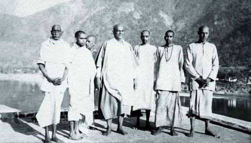 Chinmayananda standing on the right of Guru Sivananda Saraswati and other disciples, on the day of his initiation into sannyāsa on February 25, 1949, Maha Shivratri Day, Rishikesh.