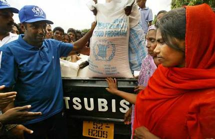 Muttiah Muralitharan takes centre stage among the refugees in a camp in Kinniya, Sri Lanka, during the Sri Lankan cricket team's delivery of much-needed food supplies. (Photo: Jason South)