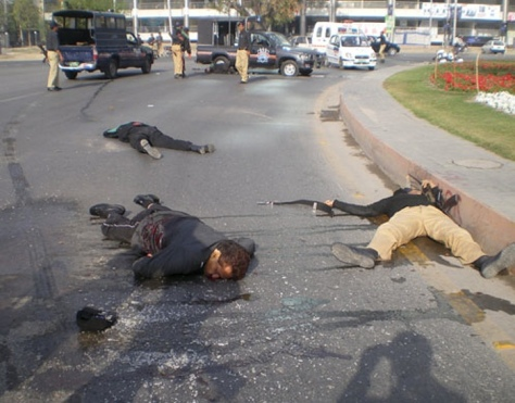 The bodies of three Pakistani police officers lie on the road (Source: theguardian.com)