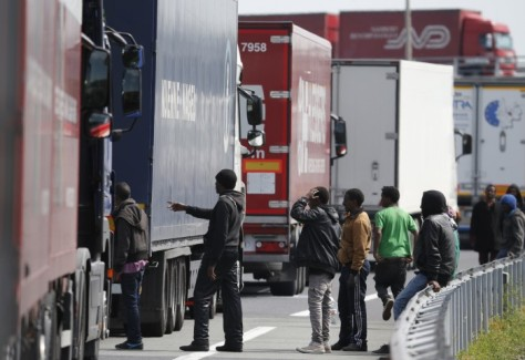 A group of migrants gathering near a line of trucks on the motorway that leads to the Channel Tunnel terminal in Calais, northern France. (Source: uk.businessinsider.com)