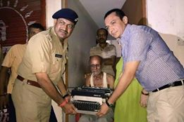 Mr. Rajesh Pandey, SSP and Mr. Raj Shekhar, the District Magistrate of Lucknow presenting a new typewriter to Kishan Kumar
