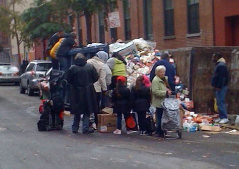 People scavenging for food in a dumpster where a Key Food supermarket has discarded spoiled food, due to power outages after Hurricane Sandy hit New York (Photo: Mr. Choppers)